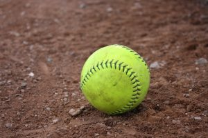 image of yellow softball on dirt