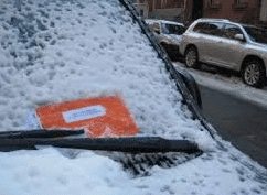 Parking Ticket on Snowy Car Windshield